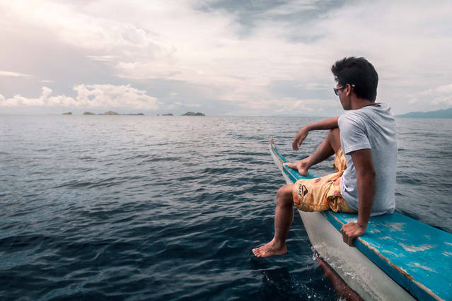 Local filipino on boat spotting Sambawan Island, Philippines