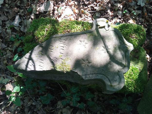 Fragment kamiennego krzyża, widoczny motyw zdobniczy w postaci trzech wyrytych gwiazdek i fragment inskrypcji pisanej kursywą