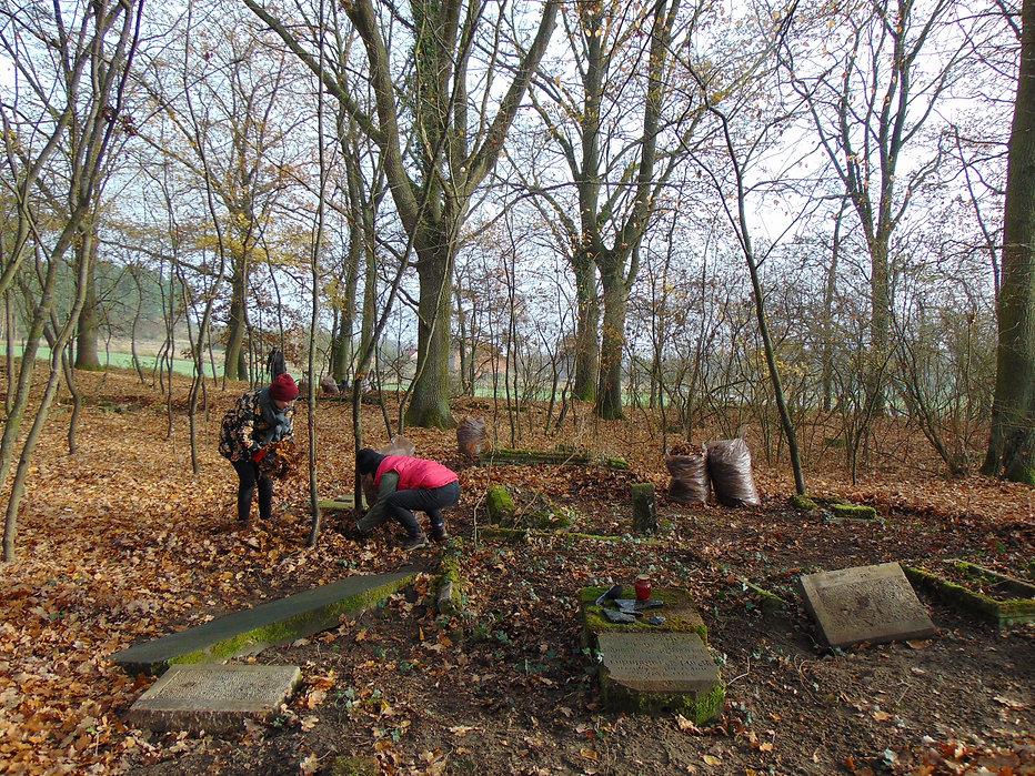 Prace porządkowe w Lubowie Drugim: oczyszczanie nagrobków z ziemi i liści
