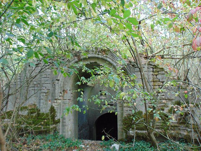 Zniszczona kaplica grobowa na cmentarzu w Wituchowie, porośnięta mchem i krzewami