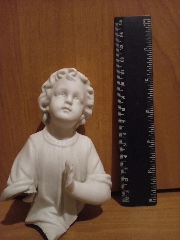 Figurka aniołka po oczyszczeniu. Aniołek ma zachowaną lewą rękę, prawa jest odłamana, podobnie jak tułów od pasa w dół. Odłamane są też skrzydła.