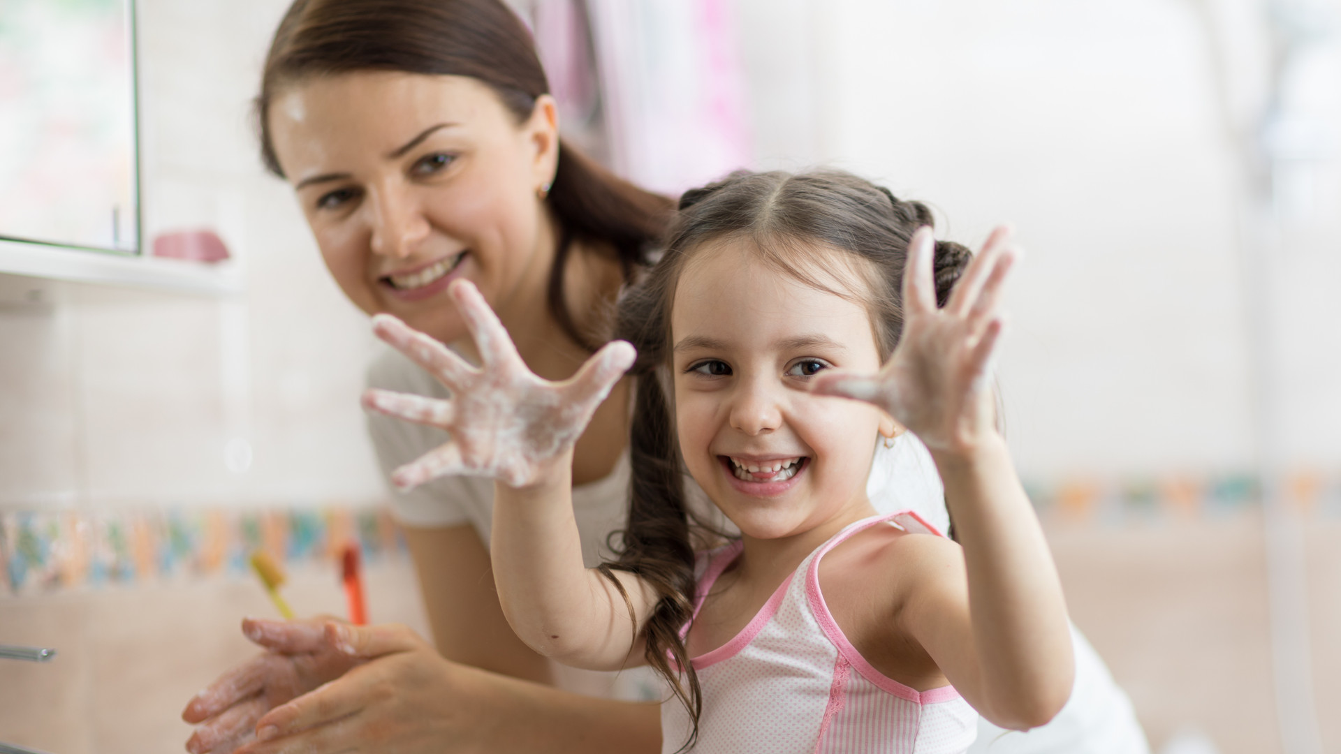 child girl and mother washing hands with