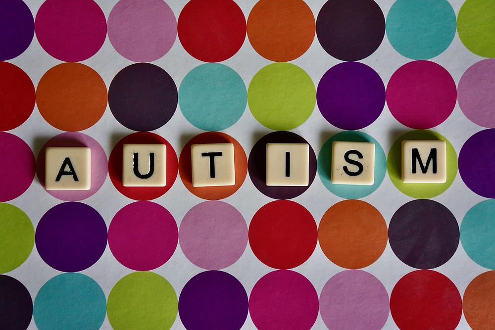 Scrabble letters spelling AUTISM on polka dot pattern
