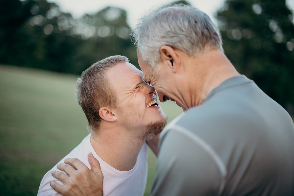 A boy with Down's syndrome smiles at an older man, perhaps his father or carer.
