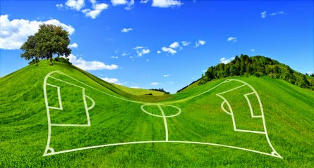 An uneven field with markings for a football pitch