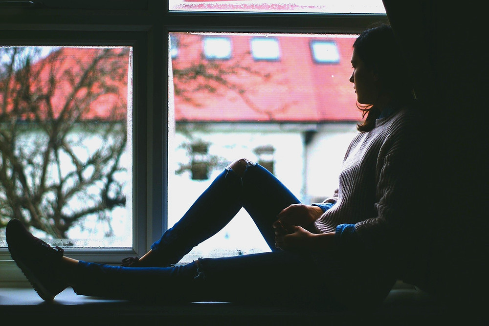 A girl sat looking out of the window