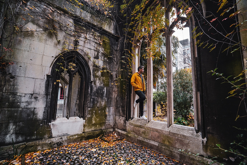 The ruins of an abandoned church with a young man looking out of a window