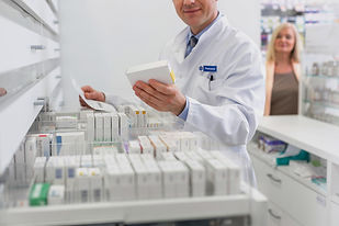 Picture of a pharmacist looking at a box of medication