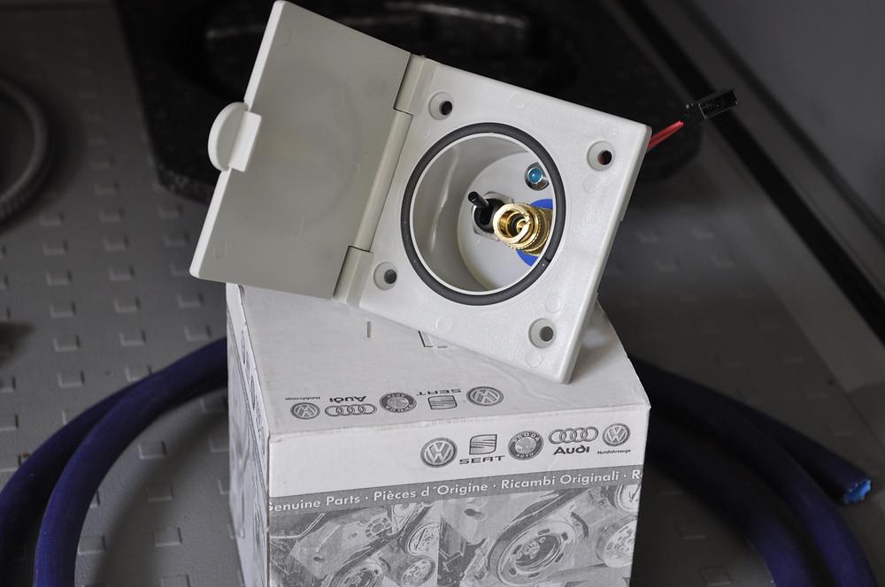 Nachrüstung der original VW Dusche für das Küchengeschränk. Der Aussenanschluss am VW California für das Frischwasser. Am Fahrzeugheck wird ein Aussenwasseranschluss aus dem Vorhandenen Frischwassertank ermöglicht. Mit der im Geschränk untergebrachten Brause lässt sich man selbst oder das Freizeitequipment abduschen.  Der Dusch-Schlauch wird mittels Schnellkupplung einfach und ohne Wasser zu vergiessen am Anschluss ein und ausgehängt. Über ein Schalter im Anschlusselement mit Betriebsleuchte, wird dann der Wasserdruck aufgebaut. Das Waschbecken kann ohne Einschränkungen weiter verwendet werden. Die Brause mit Schlauch wird elegant in einer dafür vorgesehenen Schale im Geschränk verstaut.  Die komplette nachrüstung erfolgt mit den originalen VW -Teilen, der Funktionsumfang und die Verarbeitung ist gleich der OEM Version. Der Nachrüstsatz kann auch bei uns im Onlineshop zum selber montieren bestellt werden. Unser Nachrüstsatz enthält eine Einbauanleitung, und den Notwändigen Kabelbaum & Stecker für die einfache Installation.  Im Nachrüstsatz für VW California Dusche enthalten: Anschlussmodul mit Klappe, Kupplung, Leuchte & Schalter Schrauben für Anschlussmodul Gewindebuchsen für Anschlussmodul Wasseranschluss Wasserschlauch Wasserabzweiger Kabelbaum mit Stecker Duschschlauch mit Brause Kunstoffeinlage für Dusche  Für Fragen oder Offerten stehen wir Ihnen jederzeit zur Verfügung.