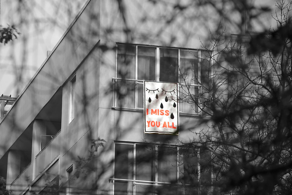 A banner with the painted image of closed eyes and tears in black with the text I MISS YOU ALL in bright orange letters. This banner hangs out a residential building window.