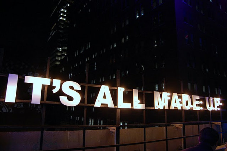 "A large sign with lightbulbs reads ""it's all made up"". this sign is illuminated and against a dark city skyline."