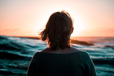 A woman looking into sunset on an ocean