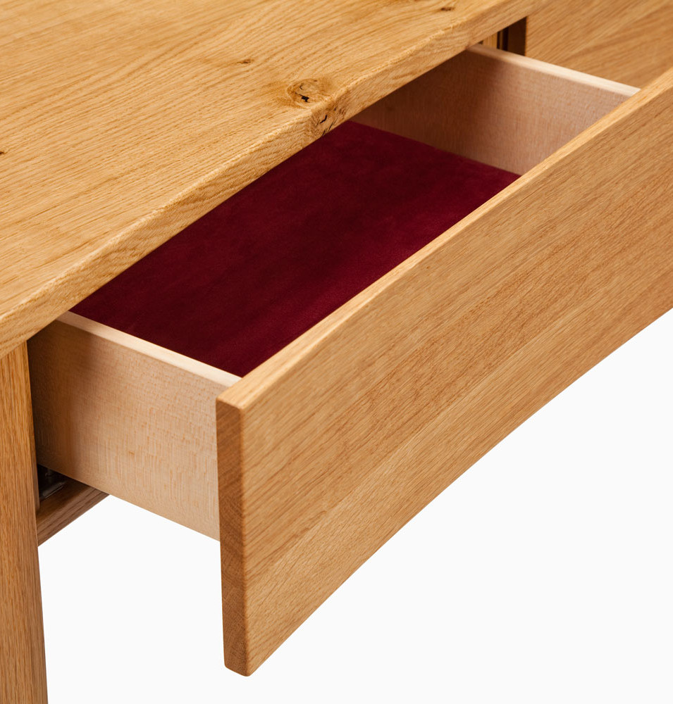The drawer fronts are curved to match the curve of the table top.