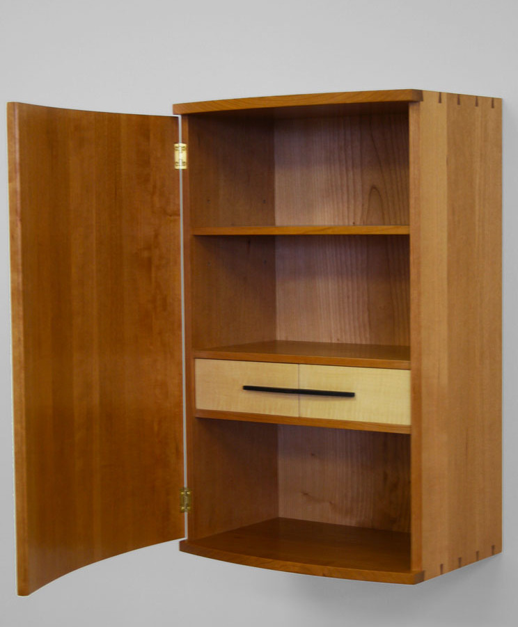 The door of the wall cabinet is coopered. Inside is an adjustable shelf and two small drawers.