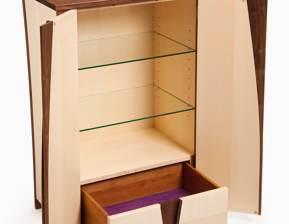 Cabinet with doors ooen showing adjustable glass shelves and drawer.