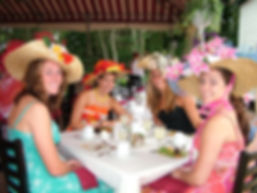 A group of young ladies show off their beautiful hats during afternoon tea.
