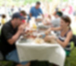 People sitting at picnic table enjoy food at the Crab Fest