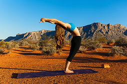 Young woman doing yoga in desert at suns