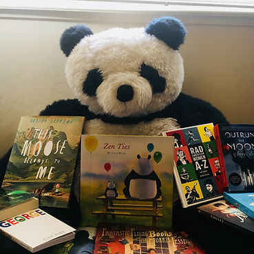 A large plush panda with picture books propped up against it.