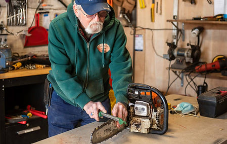 Mechanic sharpening a chainsaw.