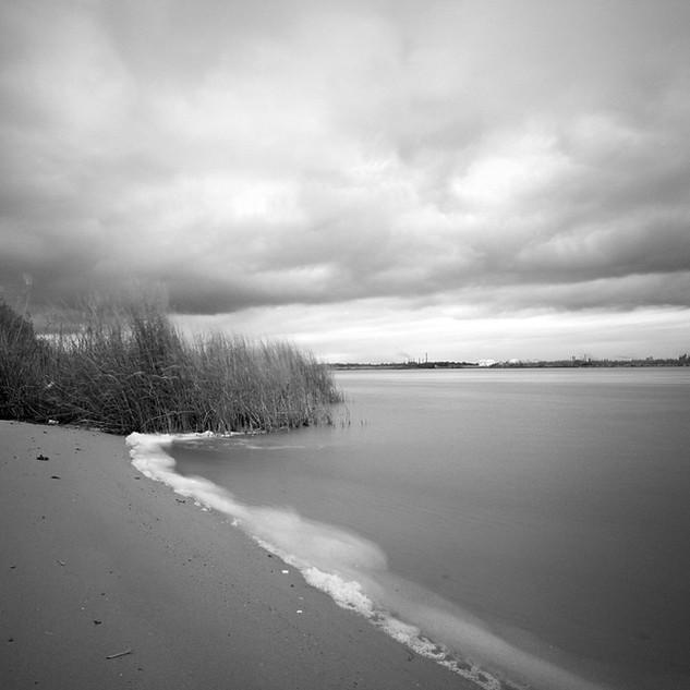 Shore, foam, and clouds