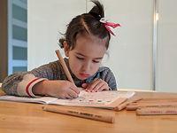 kindergarten student Maya working on a p