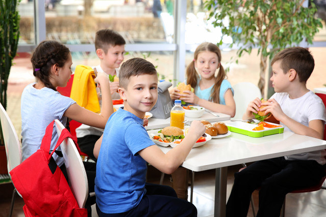 Children sitting at cafeteria table whil