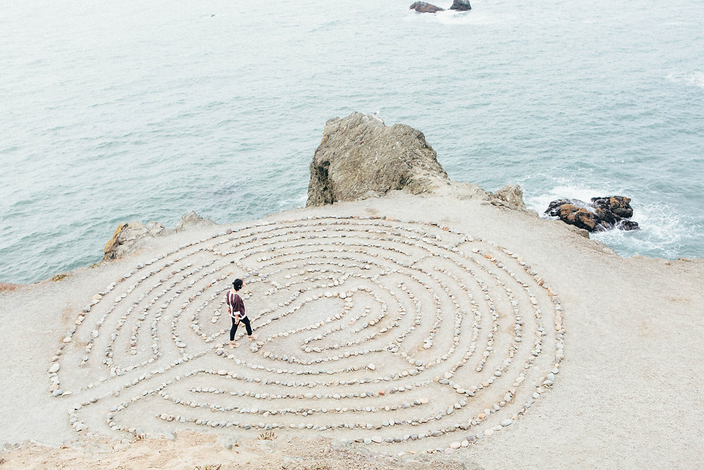 Person walks to centre of labyrinth created with pebbles on the sea shore