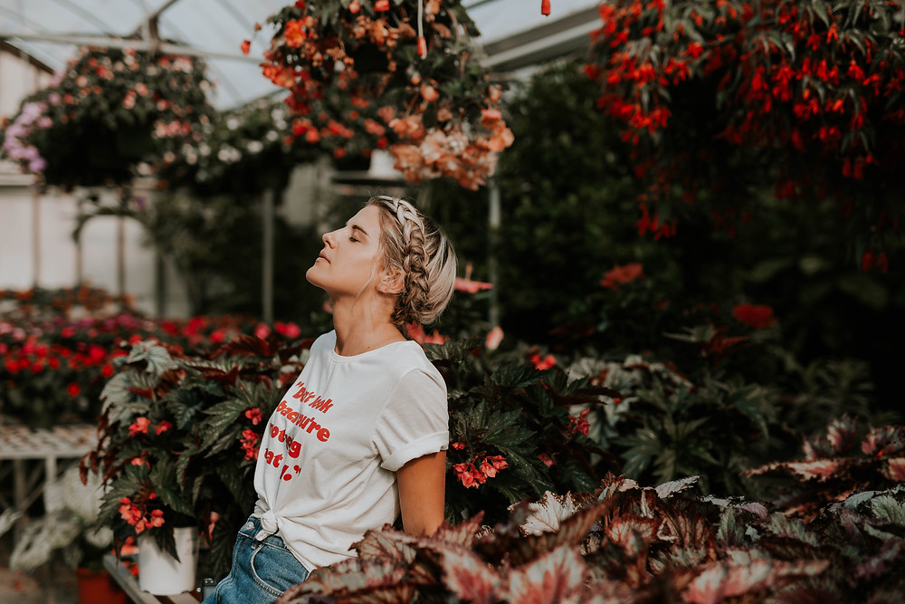 Girl with braided hair, wearing jeans and white slogan t-shirt leans back against a table in a greenhouse with her eyes closed. The tables are filled with plants with red and orange flowers and there are hanging baskets above her head