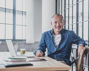 Businessman sitting at a desk, smiling.
