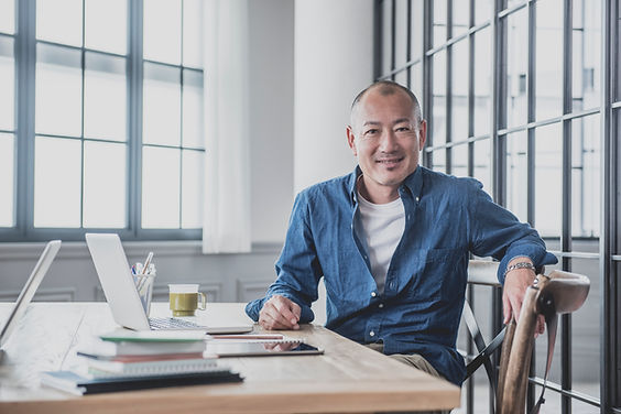 white middle aged man, balding, white round neck t-shirt, blue denim shirt, khaki pants, khaki trousers, metal wristband, squinting a the camera, in his workshop with wooden chair, with apple laptop, cup of coffee, notepads, ipad, long wooden table, windows with light streaming in