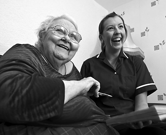Photo of an elderly women and carer laughing