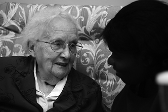Elderly woman talking to carer sitting on a sofa