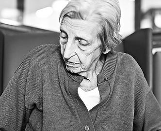 Photo of an elderly women in cardigan, looking down