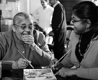 Photo of an elderly woman and volunteer at day centre laughing