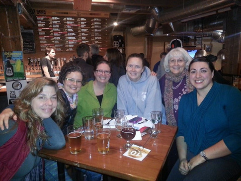 Six ORID members sitting around a table at an IPAHH event, smiling at the camera.