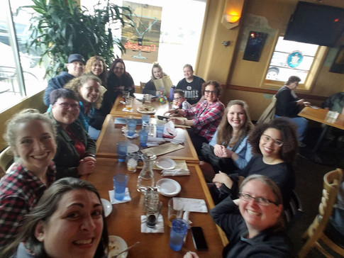 A selfie of many ORID members sitting around a long table at an IPAHH event, smiling at the camera.