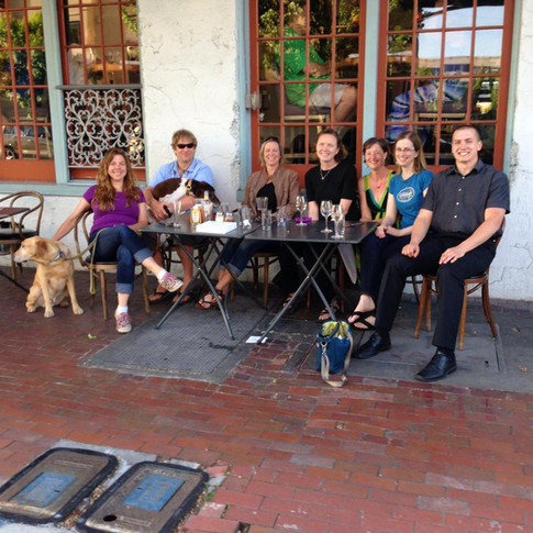 Seven ORID members sitting along one side of an outdoor table at an IPAHH event. There is a dog on the left side of the table.