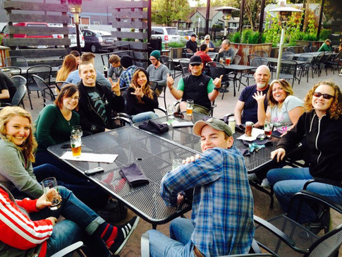 Many ORID members sitting around a table at an IPAHH event on a patio, smiling at the camera.