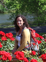 A picture of Tara wearing a backpack and sitting amongst red roses, smiling at the camera.