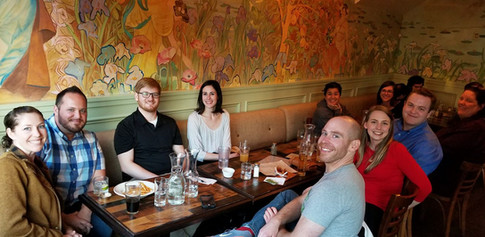 Many ORID members sitting around a table at an IPAHH event, smiling at the camera.