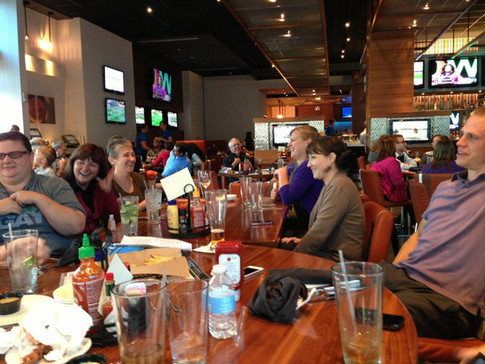 Several ORID members sitting around a table at an IPAHH event, chatting and laughing.