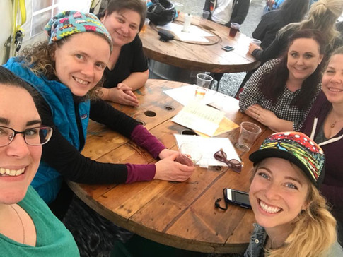 A selfie of six ORID members sitting around a table at an IPAHH event, smiling at the camera.