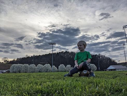 simon seated on soccer ball.JPG