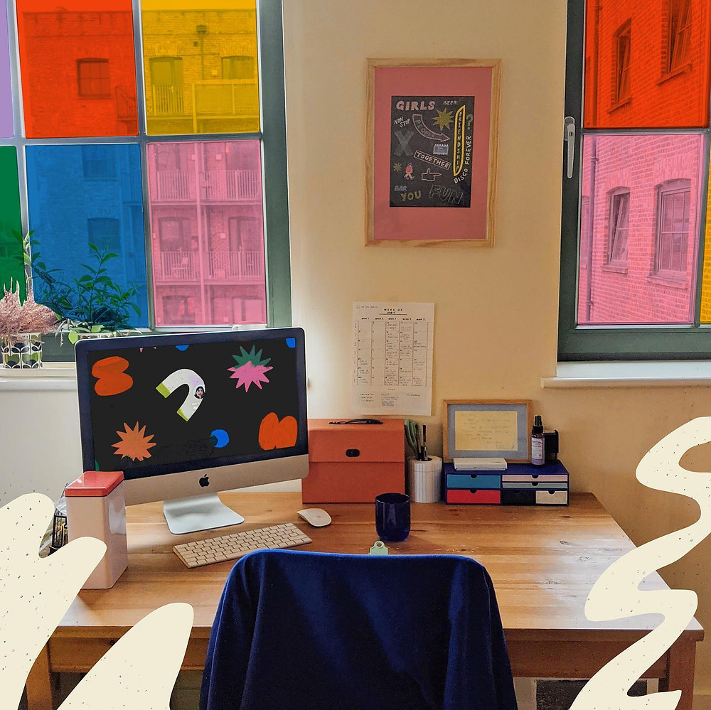 A desk with multi-coloured windows behind it.The desk has a computer and pens on it. Squiggles have been drawn on top of the photograph
