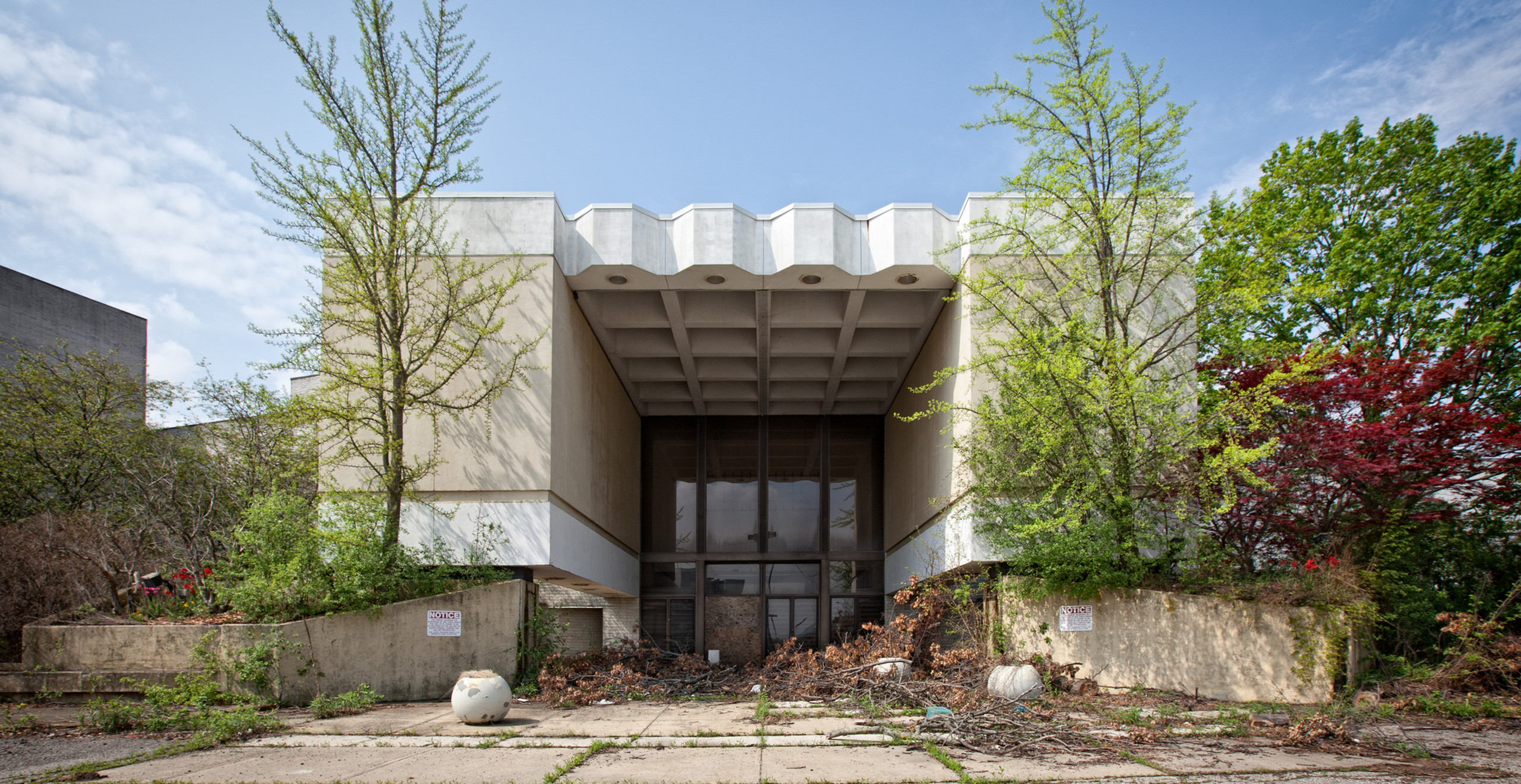 An overgrown entrance to Randall Park Mall