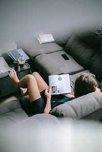 woman-sitting-on-sofa-while-reading-book