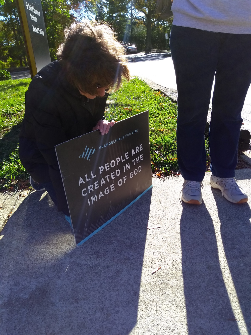 Prayer volunteer kneels in prayer with my sign.