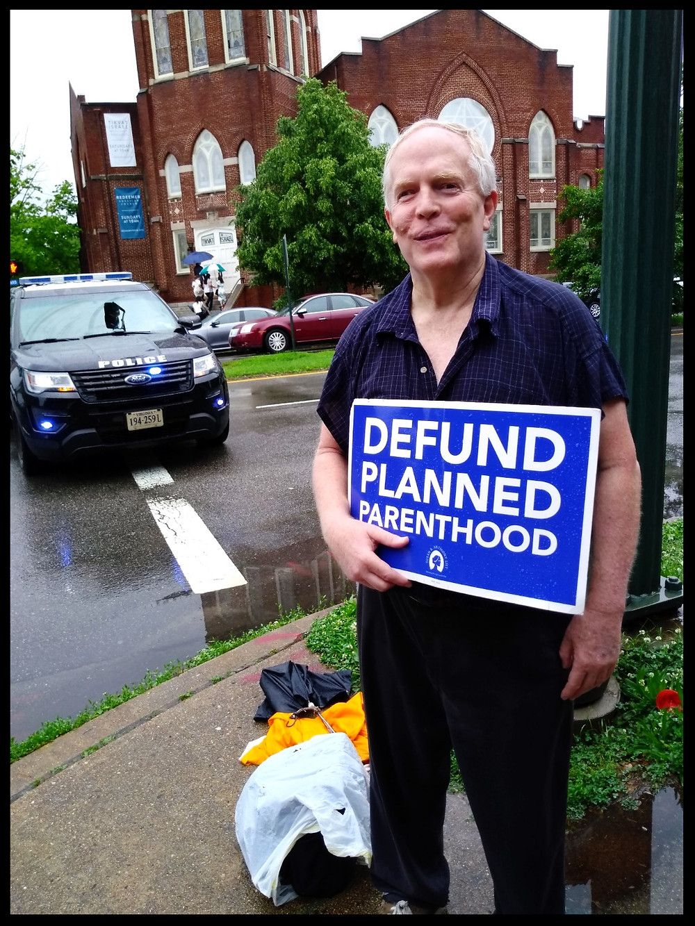 Roger stands for a photo with his sign while a police cruiser blocks traffic behind him.