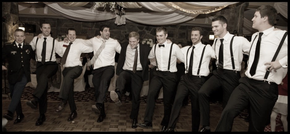 A number of my male friends dancing at a wedding.